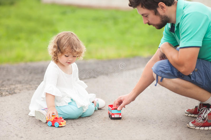 Little girl playing with toy cars with her father. Father play with his toddler daughter in boys games. Two color cars. Family leisure. Loving caring single stock photo