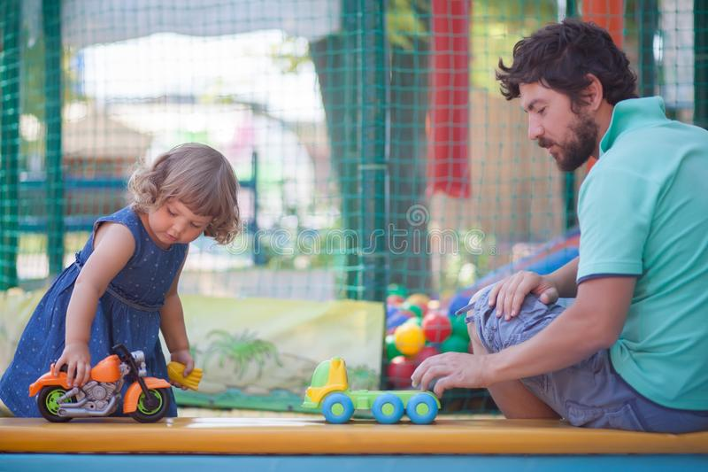 Little girl playing toy cars with her father. Father play with his toddler daughter in boys games. Two color cars. Family leisure. Loving caring single father stock images