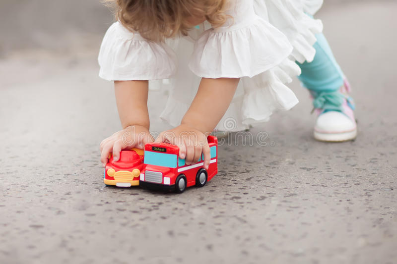 Little girl playing with toy cars outdoors. Cute toddler girl play with brothers toys - two color cars on rainy day royalty free stock photography