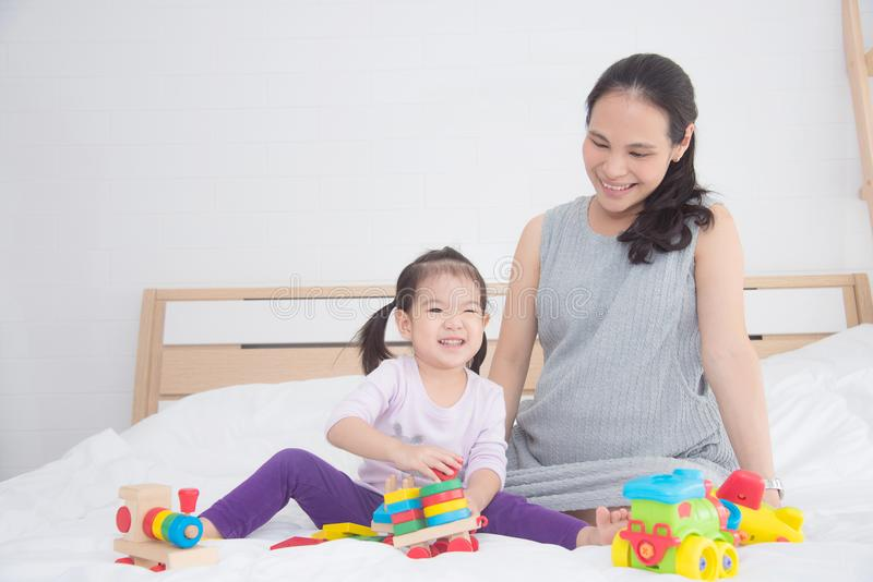 Little girl playing toy with her mother stock photo