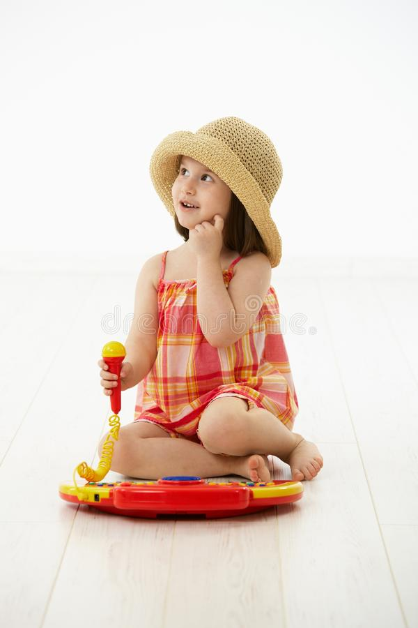Little girl playing with toy instrument. Little girl sitting on floor playing with toy music instrument, daydreaming over white background royalty free stock photography