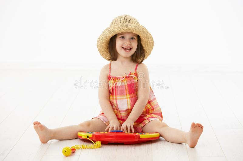 Little girl playing with toy instrument. Little girl sitting on floor playing with toy music instrument over white background stock images