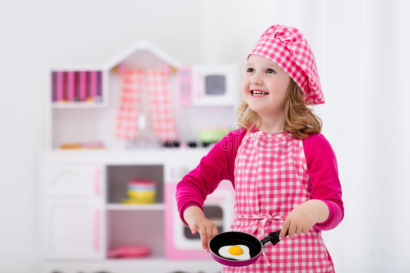 Little girl playing with toy kitchen stock images