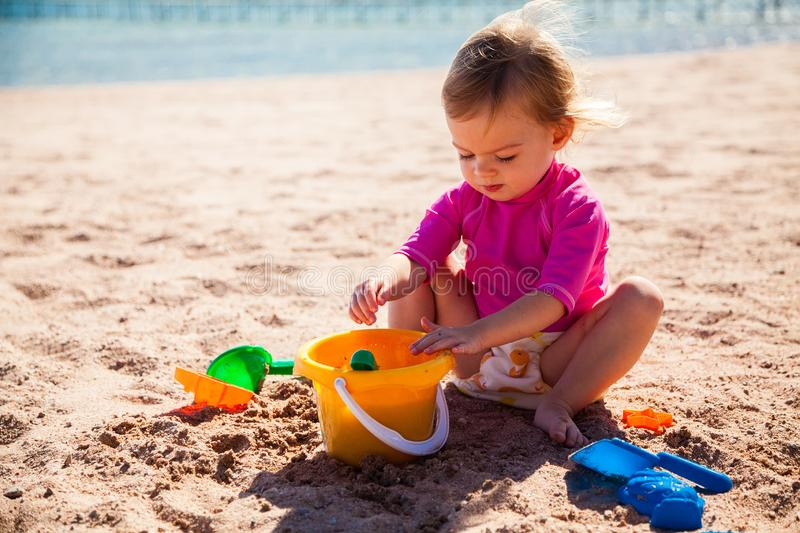 Girl playing with toys on the beach stock images