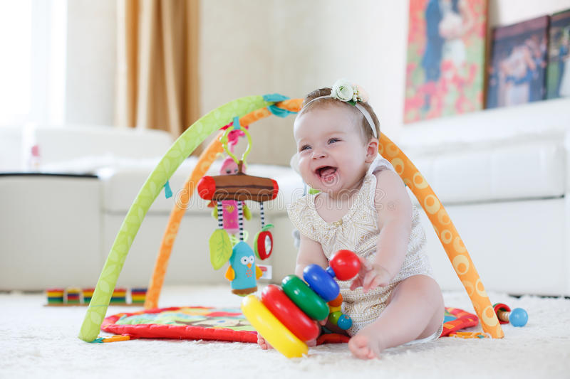 Little girl playing with toys at home on the floor stock photos