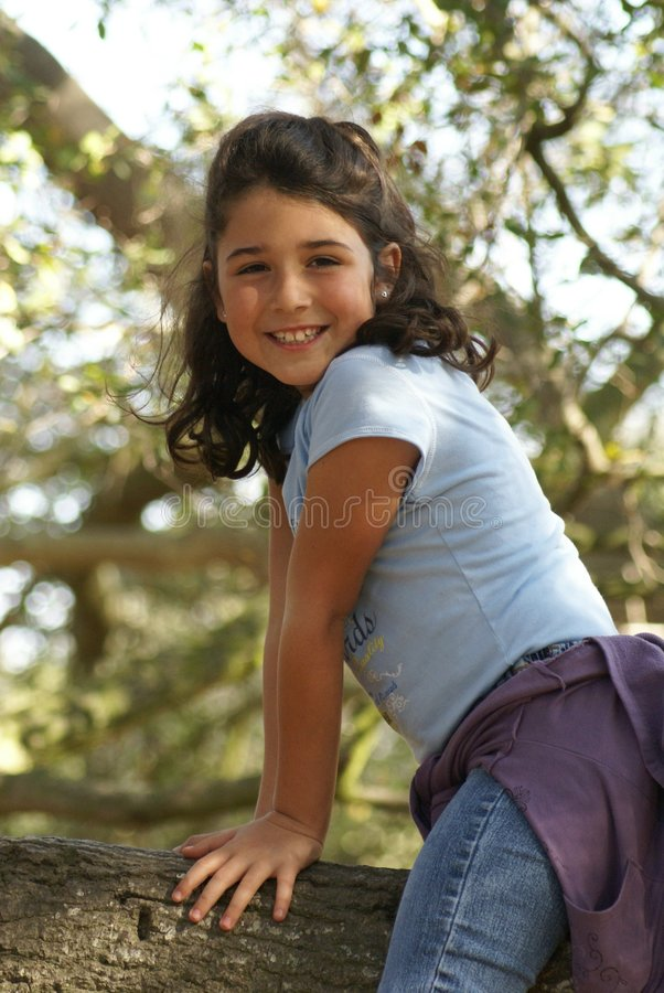 Little girl playing in tree royalty free stock photography