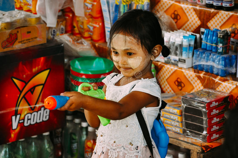 Little girl playing with water gun near Mount Popa. stock photography