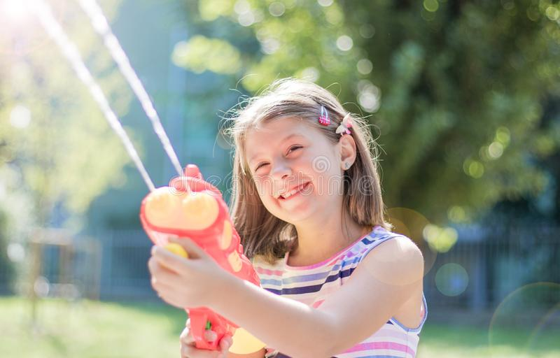 Little girl playing with water gun in the park on a sunny day royalty free stock photos