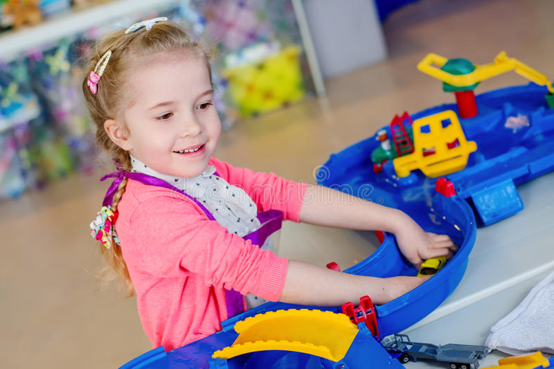Little girl playing with water and toys. Indoor stock image