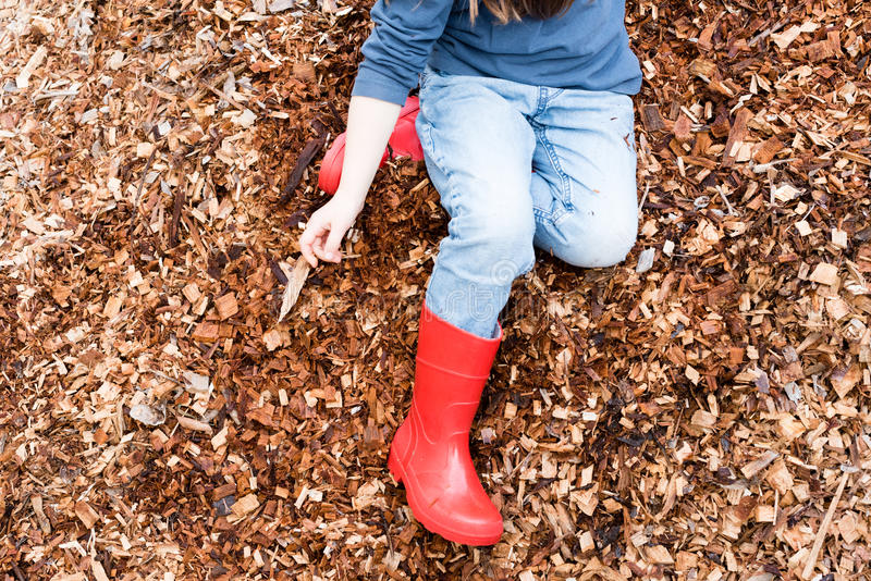 Little girl playing in wood chip pile stock photography