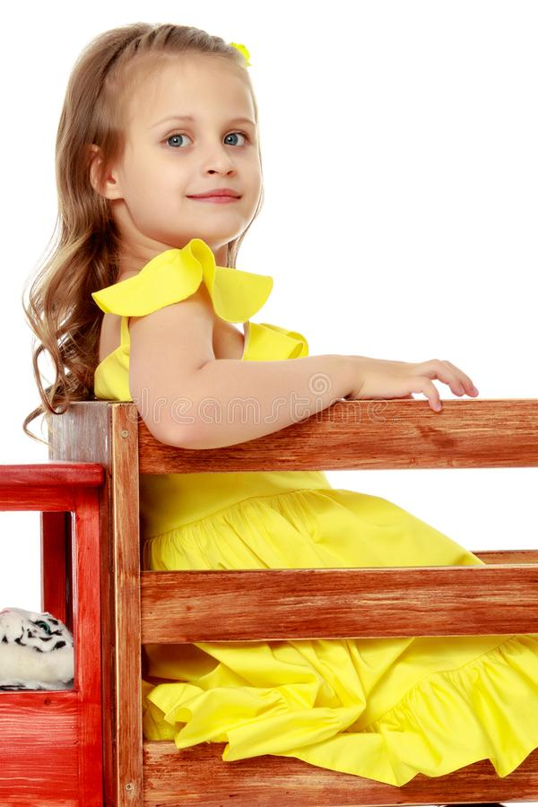 Little girl is playing with a wooden car. royalty free stock images
