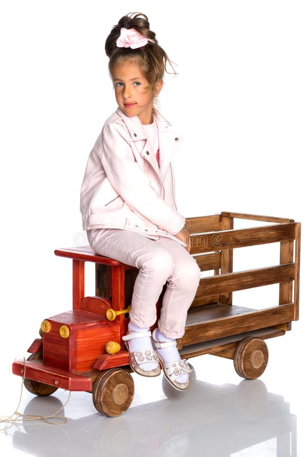 Little girl is playing with a wooden car. royalty free stock image