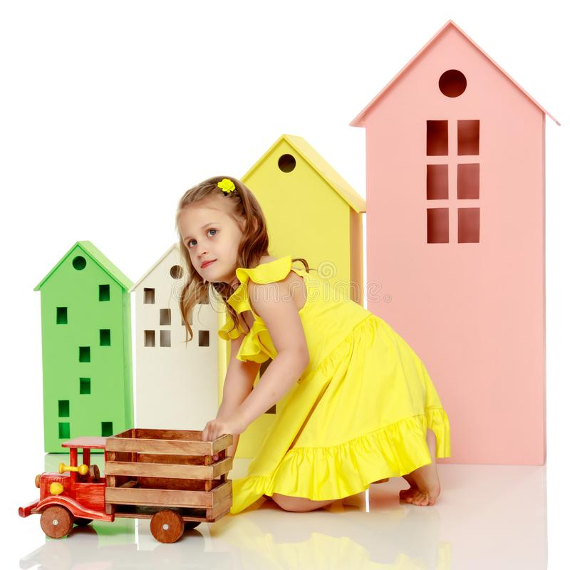 Little girl is playing with a wooden car. royalty free stock photos