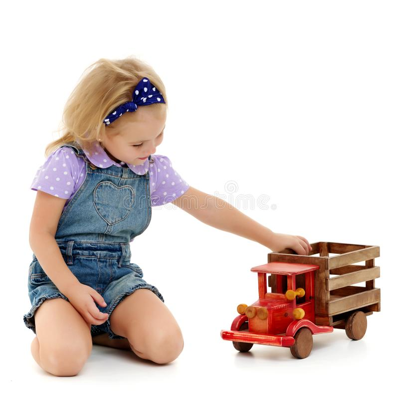 Little girl is playing with a wooden car. stock image