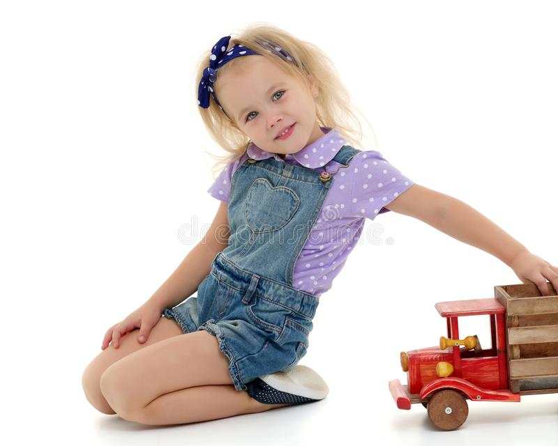 Little girl is playing with a wooden car. stock photos