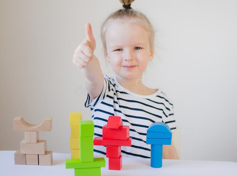 Little girl playing with wooden colorful cubes at home stock image