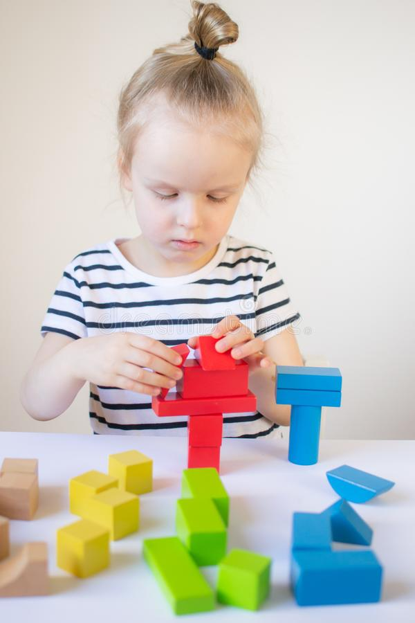 Little girl playing with wooden colorful cubes at home royalty free stock photography