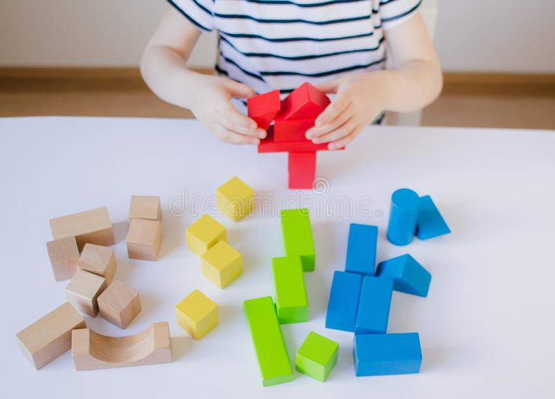 Little girl playing with wooden colorful cubes at home stock photo