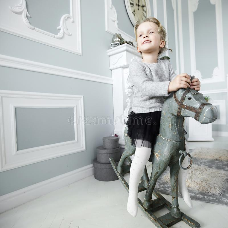 Little girl playing with a wooden horse royalty free stock image