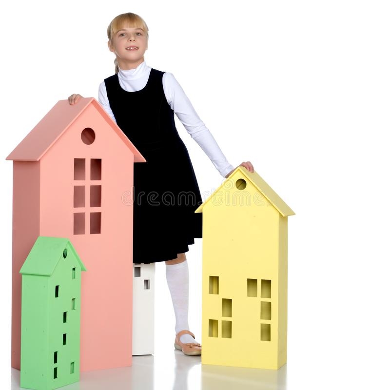 Little girl is playing with wooden houses. stock photo