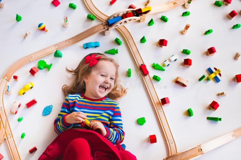 Little girl playing with wooden trains. Child playing with wooden train, rails and cars. Toy railroad for kids. Educational toys for preschool and kindergarten royalty free stock image