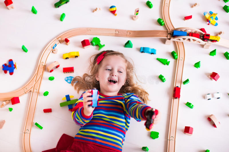 Little girl playing with wooden trains. Child playing with wooden train, rails and cars. Toy railroad for kids. Educational toys for preschool and kindergarten stock photography