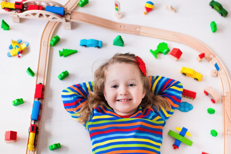 Little girl playing with wooden trains. Child playing with wooden train, rails and cars. Toy railroad for kids. Educational toys for preschool and kindergarten stock photo