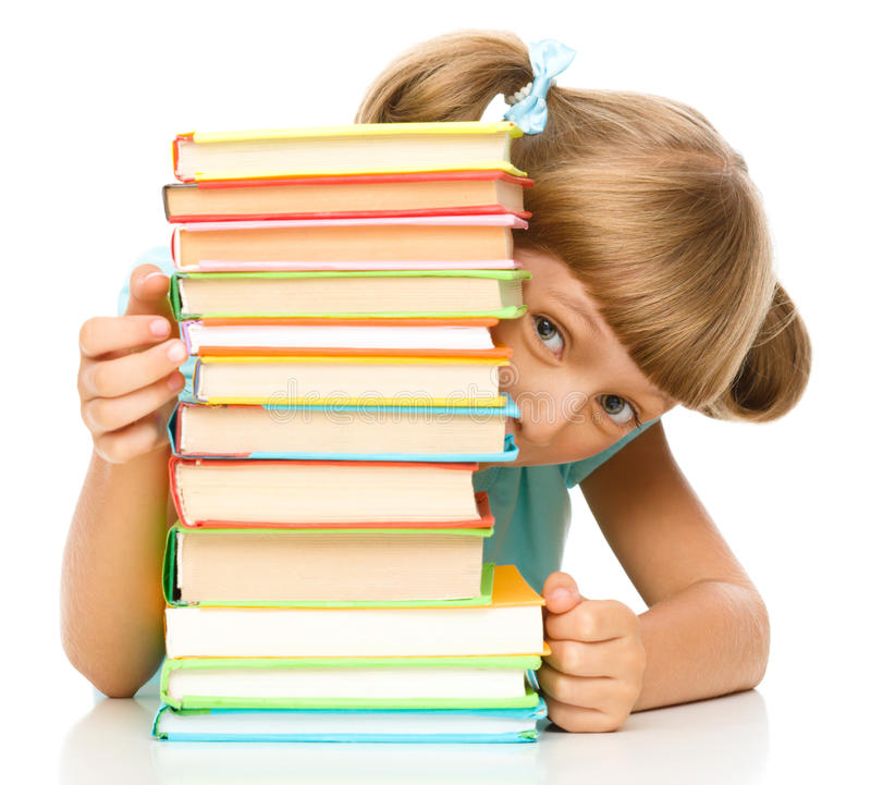 Little girl plays with book. Cute little girl plays with pile of books while sitting at table, isolated over white stock photography