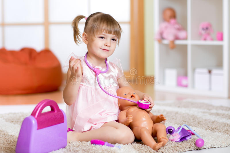 Little girl plays doctor examining a doll patient royalty free stock photography