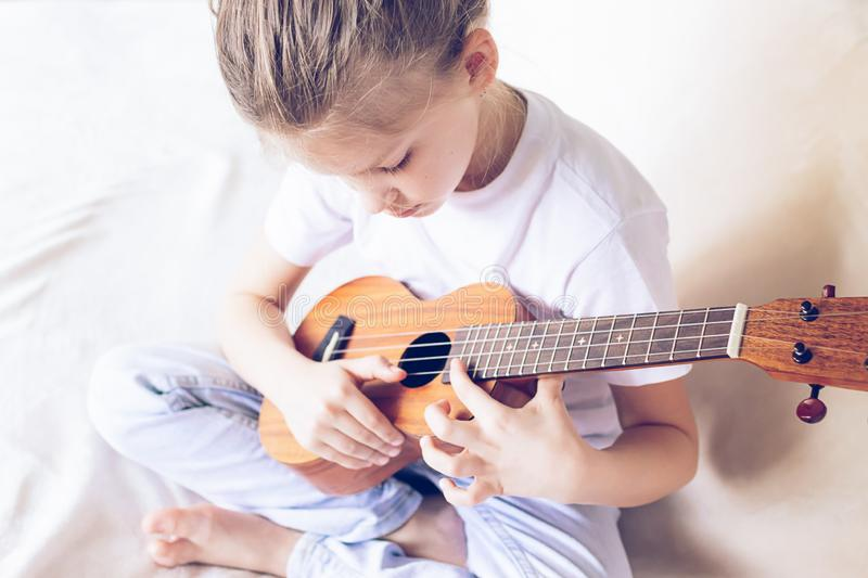 A little girl plays guitar in her home. Selective focus. Close-up. The concept of music and art stock photos