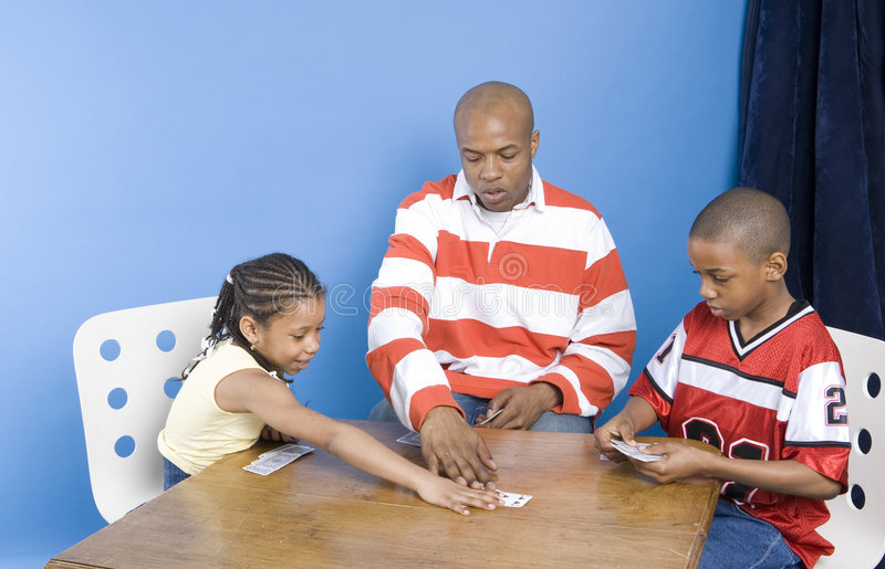 Little girl plays her card. Family playing card game at the table royalty free stock photo