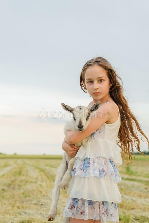 Little girl plays and huhs goatling in country, spring or summer nature outdoor. Cute kid with baby animal, countryside, forest, royalty free stock photo