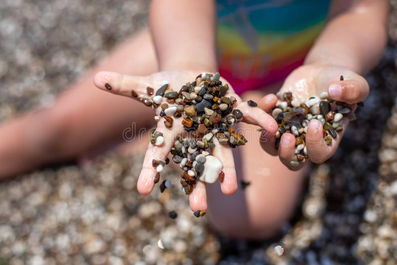 A little girl plays on a pebble beach. The development of fine motor skills. Large grains of sand on the beach.  stock images