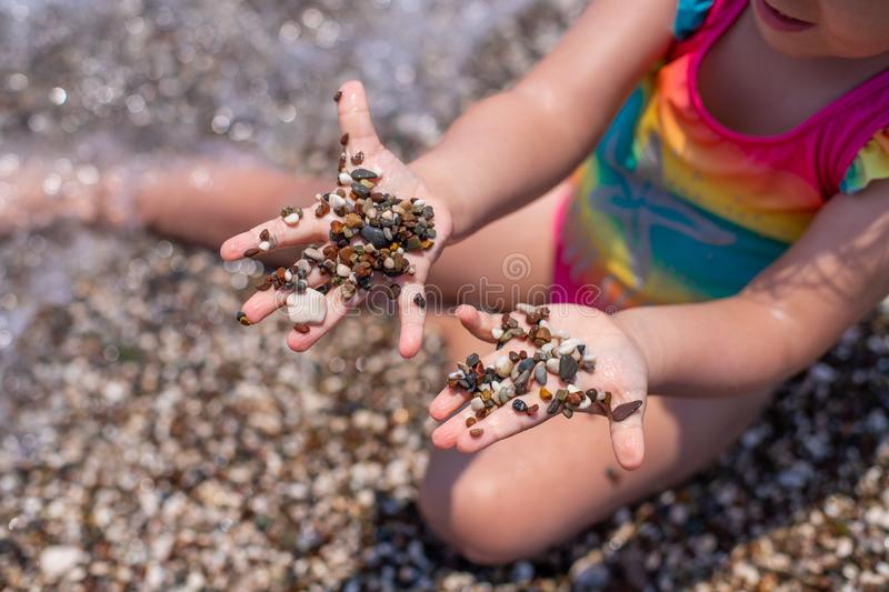 A little girl plays on a pebble beach. The development of fine motor skills. Large grains of sand on the beach.  stock image