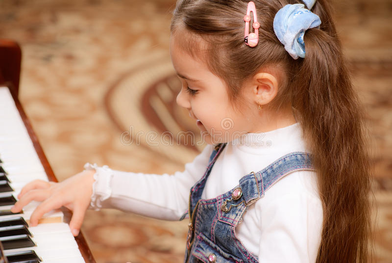 Little girl plays piano royalty free stock image