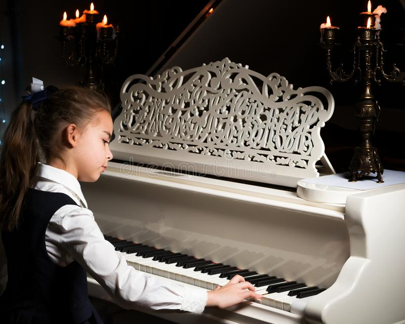 Little girl plays the piano by candlelight. royalty free stock photography