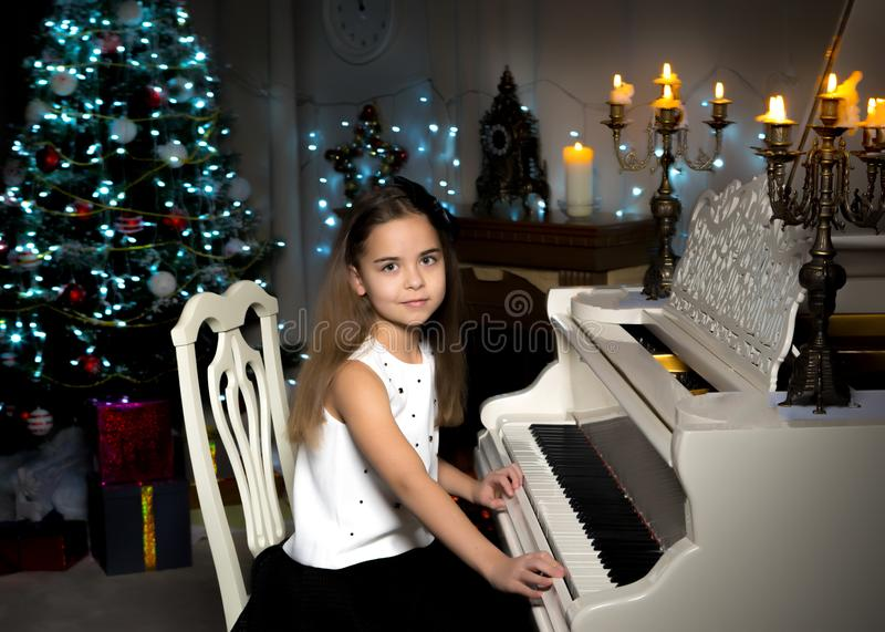 Little girl plays the piano by candlelight. stock images