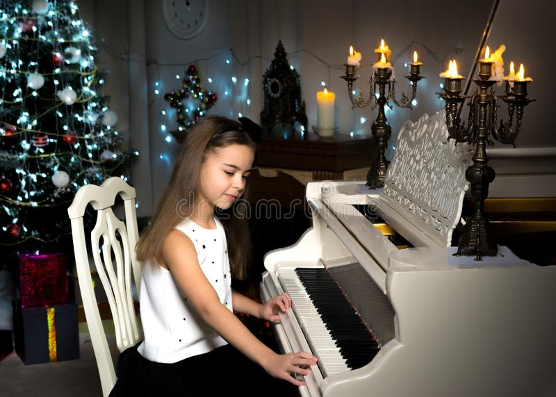 Little girl plays the piano by candlelight. royalty free stock images