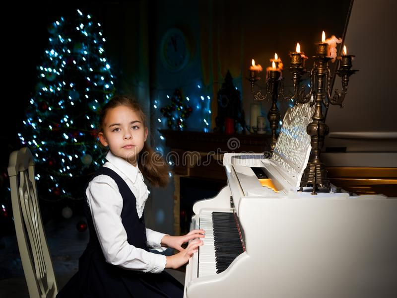 Little girl plays the piano by candlelight. royalty free stock photo