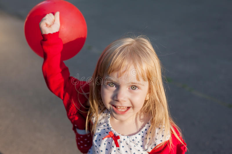 Little girl plays with red ball stock photo