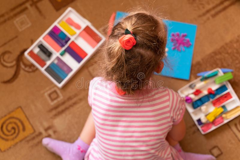 A little girl plays and sculpts from clay. modeling of plasticine and the development of fine motor skills royalty free stock image