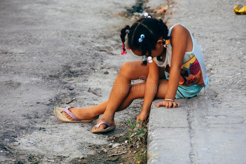 A little girl plays with a stone in Havana city, Cuba. A little girl plays with a stone on the side of the street in Havana city, Cuba stock image