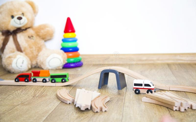Little girl plays with toys, wooden railway and train. copy space. stock photos