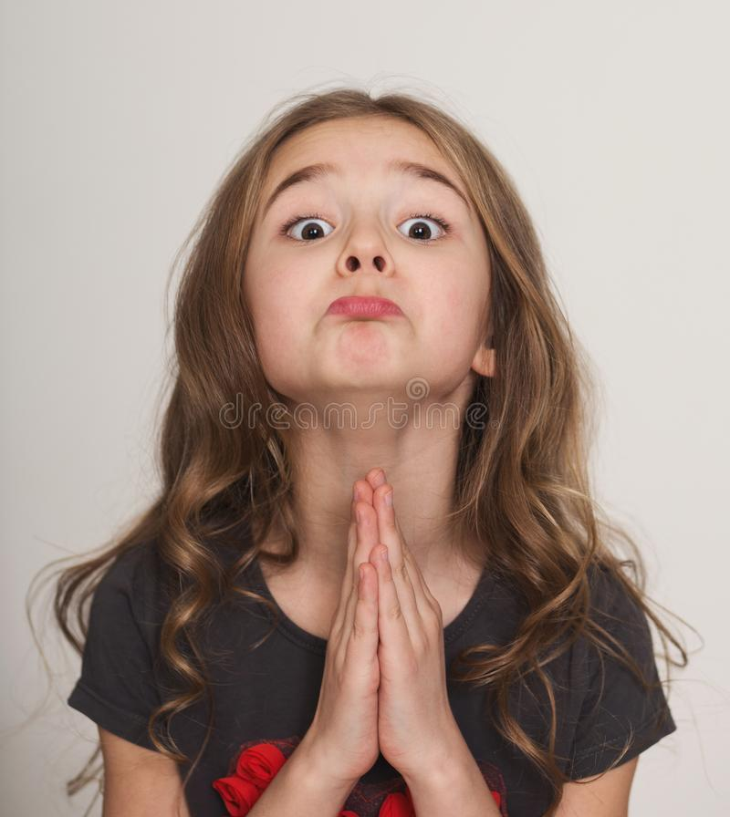 Little girl pleading with hands clasped together royalty free stock images
