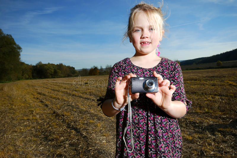 Little girl with pocket camera royalty free stock photography