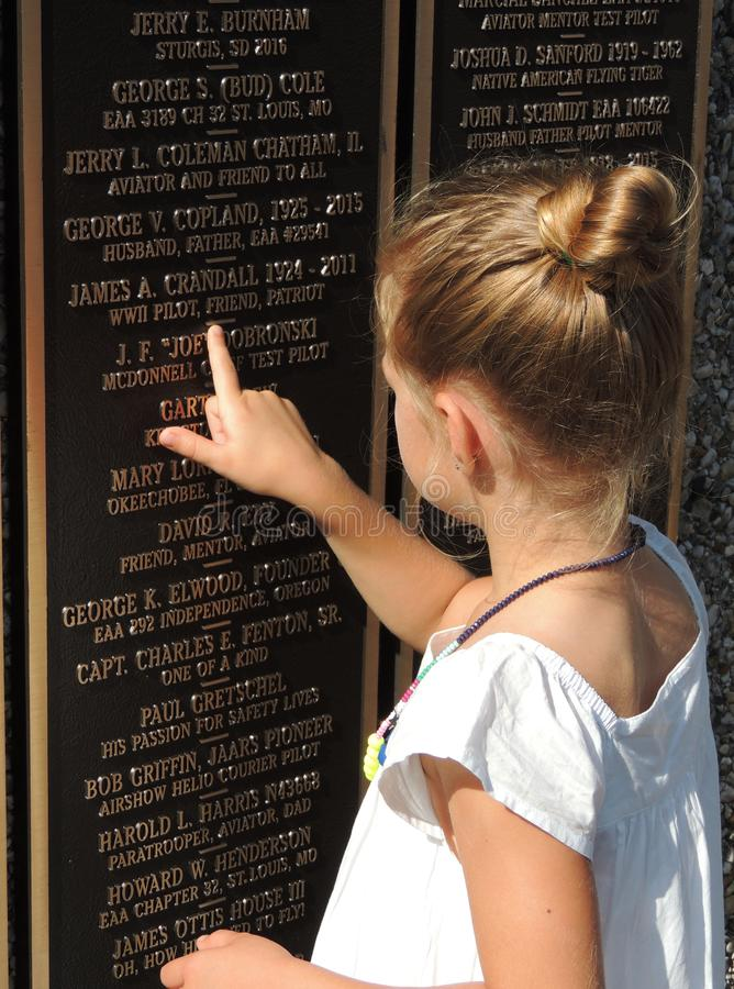 Little girl points to a loved ones name on EAA Memorial Wall in Oshkosh, WI stock photography