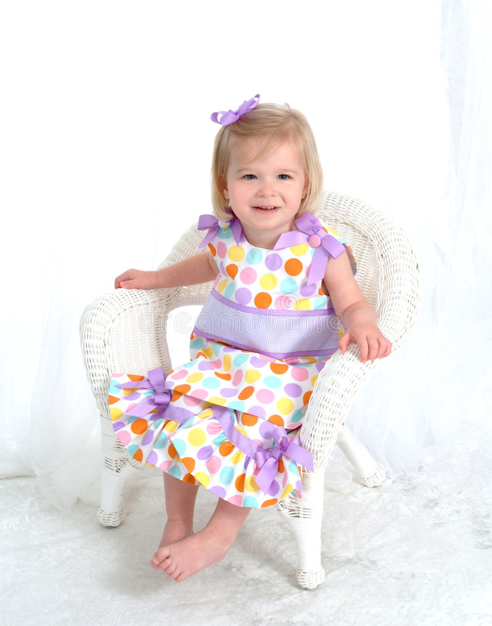 Little Girl in Polka Dot Dress. Full length of smiling blond girl in colorful polka dot dress sitting on chair in front of white background stock photography