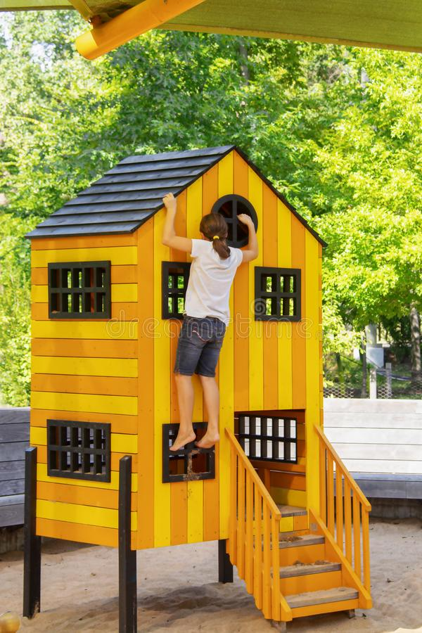 Little girl with pony tail and sandy feet climbs playhouse on playground in the Gathering Place public park in Tulsa OK.  stock photos