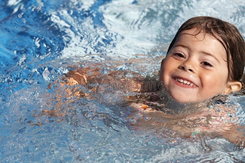 Little girl in pool stock photography