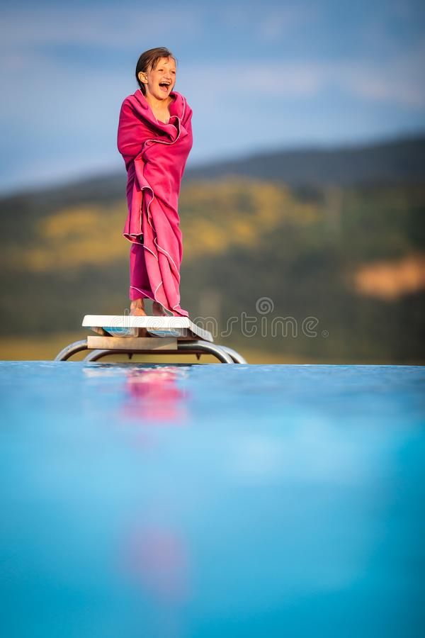 Little girl on a pool`s edge, learning to swim and dive. stock photos